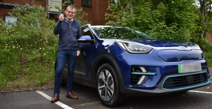 Photo of blue Kia ENiro with Simon Carlin, MD of The Lost Coin Financial Planning
